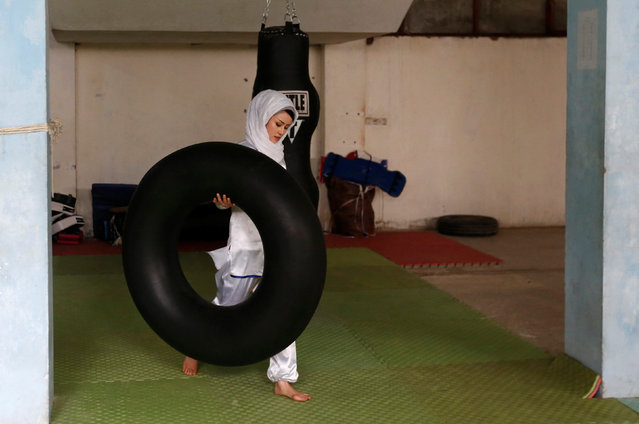 """Sabera Bayanne, 20, a student at the Shaolin Wushu club, carries a tube before an exercise in Kabul, Afghanistan January 29, 2017. On a snowy mountaintop to the west of Kabul, a group of Afghan girls practise the flowing movements of Wushu, a sport developed from ancient Chinese kung fu martial arts, stretching and bending and slashing the air with bright swords. In a country where women's sport is severely restricted, the Shaolin Wushu club in a part of Kabul that is home to the capital's Hazara ethnic community, is a rare exception. Sima Azimi, the 20-year-old leading the practice session, says Wushu teaches self-defence, but just as important, """"it's really effective for body and soul"""". Martial arts of all kinds are popular in Afghanistan, but it is a notoriously hard country for women, and the girls of the Shaolin Wushu club face regular harassment and abuse in addition to the normal dangers of life in Kabul. When possible, training goes on in a gym dominated by a poster of Hussain Sadiqi, a Hazara martial arts champion who fled to Australia in 1999 and later worked as a film stuntman. So far, all the girls in the club are Hazara, a Persian-speaking, mainly Shi'ite group who have faced a series of attacks claimed by Islamic State militants over the past year. (Photo by Mohammad Ismail/Reuters)"""