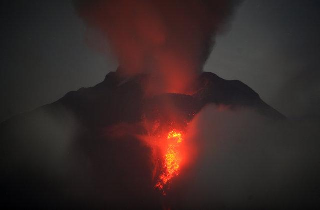 Mount Sinabung spews lava and gas during its eruption as seen from Jeraya, North Sumatra, Indonesia, early Monday, January 20, 2014. (Photo by Binsar Bakkara/AP Photo)