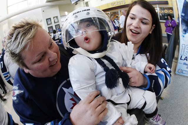 Winnipeg Jets fans Corie, Erica and Chantelle Naugle are dressed in white – some more than others – as they arrive for Game 4 of a first-round NHL hockey playoff series between the Jets and the Anaheim Ducks, Wednesday, April 22, 2015, in Winnipeg, Manitoba. (Photo by John Woods/The Canadian Press via AP Photo)