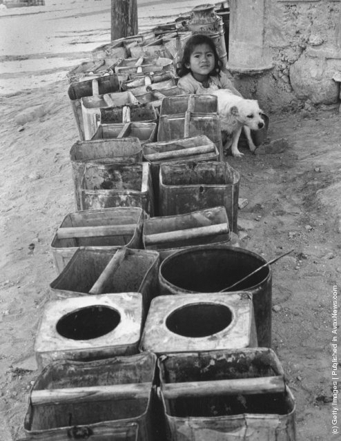 A queue of tins in front of the water tap in a Peruvian town awaits the advent of the day of water, when the townspeople will collect their supply of water, 1955