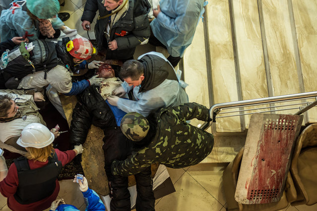 Medics tend to a gravely wounded anti-government protester in the lobby of the Hotel Ukraine, which has been converted to a medical clinic and makeshift morgue, on February 20, 2014. (Photo by Brendan Hoffman/Getty Images)