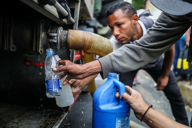 A group of people is supplied with water from a tanker in Caracas, Venezuela, 31 March 2019. The lack of water caused by a week of blackouts in Venezuela ended up pushing Venezuelans into the streets to protest against the government of Nicolas Maduro in a day in which there were clashes in Caracas with gunfire and it is not yet known if anyone was injured. (Photo by Miguel Gutierrez/EPA/EFE)