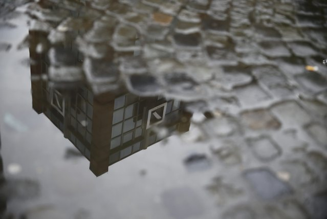 A Deutsche Bank office is reflected in a puddle in Hanau, Germany, April 27, 2015. (Photo by Kai Pfaffenbach/Reuters)