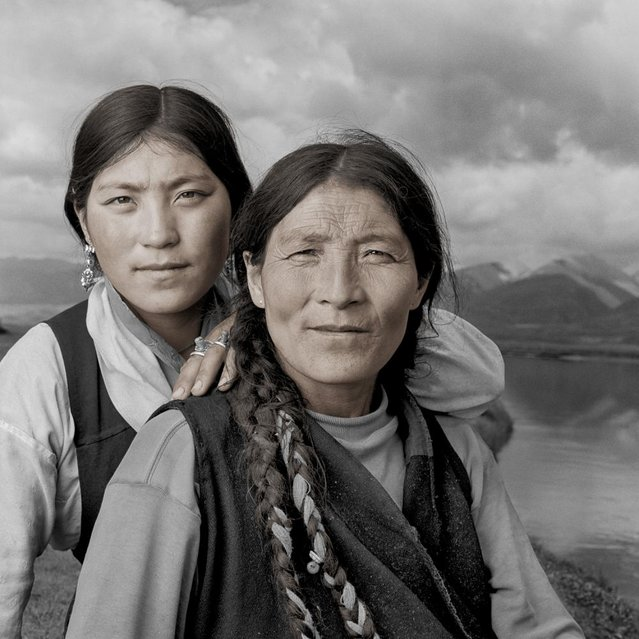 """Samdo & Kunga. Kunga was braiding her mother's hair as I walked into their camp. It was mid morning and they were just about to cross the river to retrieve their goats for the morning milking. They motioned for me to join them as they waded across the ice-cold river. We each grabbed a goat by the horns and led/floated them back across to their camp. The rest of the herd followed"". (Phil Borges)"