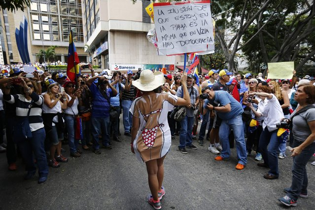 An anti-government protester holds up a sign as she poses for photographers during a march in Caracas March 2, 2014. Thousands of Venezuelans have escaped to the beach for the long Carnival weekend, heeding President Nicolas Maduro's call to leave behind nearly a month of anti-government protests. Inflation, violent crime, and political differences that divide Venezuelans have fed the country's worst unrest for a decade, where at least 17 people were killed. (Photo by Jorge Silva/Reuters)