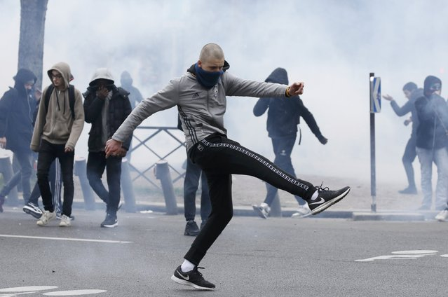 Clouds of tear gas surround youths as they face off with French police during a demonstration against police brutality after a young black man, 22-year-old youth worker named Theo, was severely injured during his arrest earlier this month, in Paris, France, February 23, 2017. (Photo by Gonzalo Fuentes/Reuters)