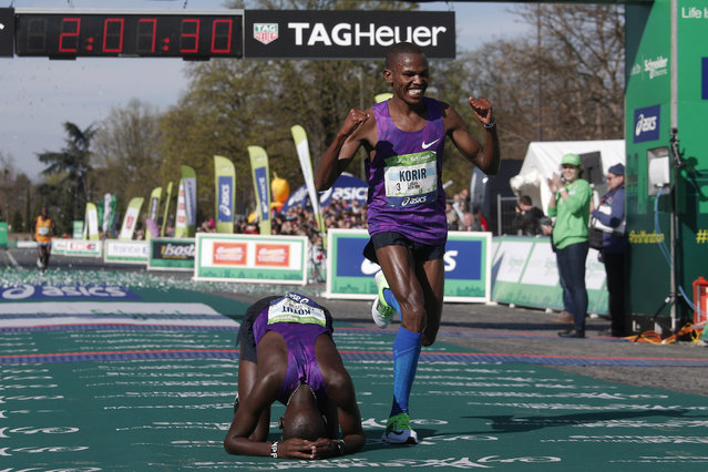 Cyprian Kotut of Kenya, left, rests after winning the 40th Paris Marathon men's race, as Laban Korir  of Kenya, right, celebrates second place, in Paris, Sunday April 3, 2016. Cyprian Kotut won the Paris marathon on Sunday as Kenyan runners pulled off a podium sweep in perfect weather conditions. The 24-year-old Kotut, who also won the Paris half-marathon last month, completed the 42.195-kilometer (26-mile) race in 2 hours, 7 minutes and 11 seconds to improve his personal best set last year when finishing runner-up in Milano on his debut over the distance (2:08.55). (Photo by Thibault Camus/AP Photo)