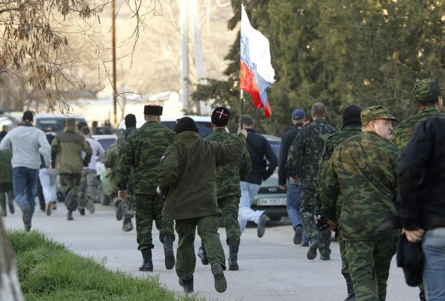 Members of pro-Russian self-defence units move in the direction of a military airbase as they attempt to take over in the Crimean town of Belbek near Sevastopol March 22, 2014. (Photo by Vasily Fedosenko/Reuters)
