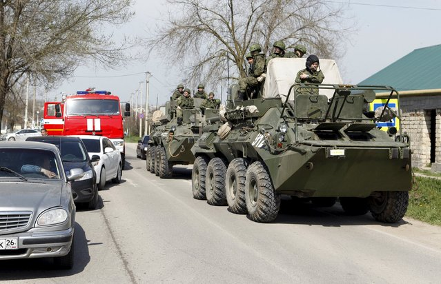 Servicemen of the Russian armed forces ride on armoured vehicles in a settlement of the Novoselitsky district, where a local police station was recently attacked, in Stavropol region, southern Russia, April 11, 2016. (Photo by Eduard Korniyenko/Reuters)