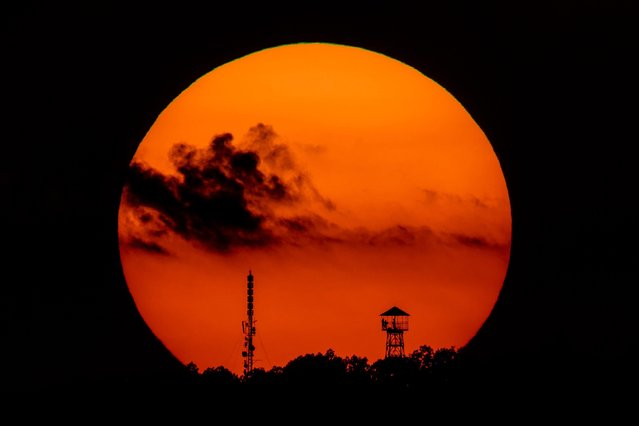 The setting sun frames a look-out tower and a telecommunication transmission tower near Salgotarjan, some 100km northeast of Budapest, Hungary, Wednesday, August 22, 2018. (Photo by Peter Komka/MTI via AP Photo)