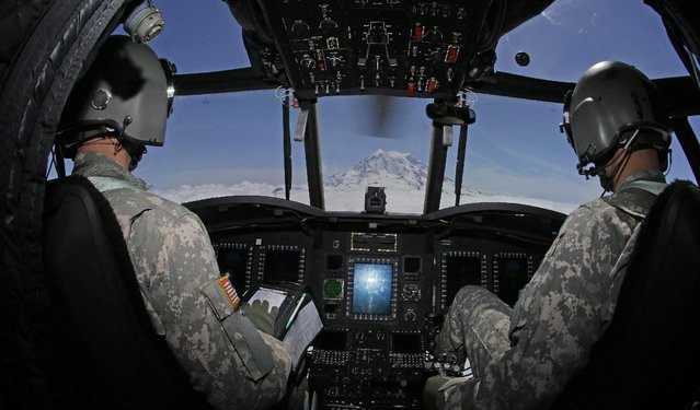 In this photo taken May 15, 2015, U.S. Army Reserve Capt. Justin King, right, and Chief Warrant Officer 2 Christopher Scott, left, fly a U.S. Army Reserve Boeing CH-47F Chinook helicopter flies near Mount Rainier in Washington state during a search and rescue training mission. (Photo by Ted S. Warren/AP Photo)