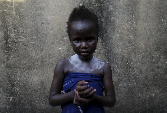 Mariam Tchinda, 6, stands at her home in Cocody Danga slum in Abidjan May 25, 2015. (Photo by Luc Gnago/Reuters)
