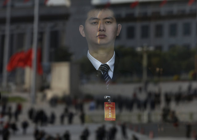 A security person stands guard while the Tiananmen Square is reflected on the glass at an entrance of the Great Hall of the People where the opening session of the 18th Communist Party Congress is held in Beijing, China Thursday, November 8, 2012. (Photo by Vincent Yu/AP Photo)