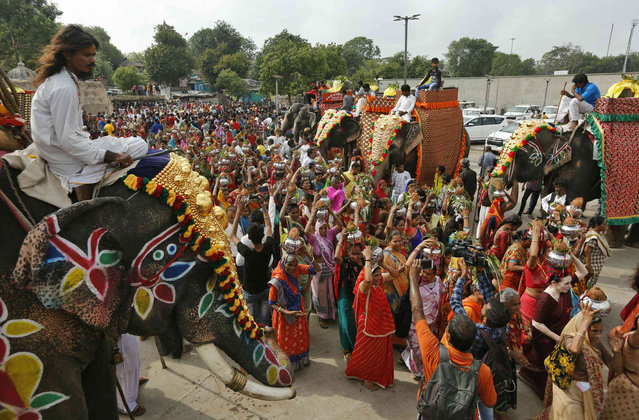 Devotees walk past caparisoned elephants carrying pots on their heads to fill water from the Sabarmati River during the Jal Yatra procession ahead of the annual Rath Yatra or chariot procession of Hindu deity Lord Jagannath in Ahmadabad, India, Monday, June 17, 2019. The water from the Sabarmati river, considered holy by devotees is carried and used for rituals of the idols which are then carried in a procession in specially made chariots during the Rath Yatra or chariot festival scheduled to be celebrated on July 4, 2019. (Photo by Ajit Solanki/AP Photo)