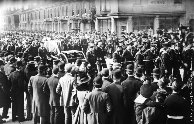 Sailors pulling a gun carriage and coffin through the streets of Portsmouth during a naval funeral, 1890s. A large crowd has gathered to pay their respects