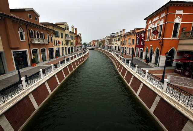 A canal flows through the center of the Florentia Village in the district of Wuqing, located on the outskirts of the city of Tianjin June 13, 2012. The shopping center, which covers an area of some 200,000 square meters, was constructed on a former corn field at an estimated cost of $220 million and copies old Italian-style architecture with Florentine arcades, a grand canal, bridges, and a building that resembles a Roman Coliseum. (Photo by David Gray/Reuters)