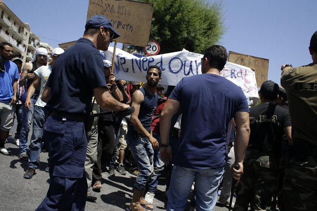 Coast guard scuffle with Syrians during a protest by refugees and migrants, demanding better living conditions and faster processing of their asylum registrations at the port of Mytilene, on the northern Greek island of Lesvos on Wednesday, June 17, 2015. The Aegean island has borne the brunt of a huge influx of migrants from the Middle East, Asia and Africa crossing from Turkey to nearby Greek islands. More than 50,000 migrants have arrived in Greece so far this year. (AP Photo/Thanassis Stavrakis)