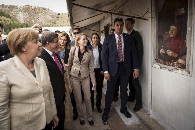 German Chancellor Angela Merkel and Turkish Prime Minister Ahmet Davutoglu are welcomed by refugees living in Nizip refugee camp near Gaziantep, Turkey, April 23, 2016. (Photo by Steffen Kugler/Reuters/Bundesregierung)