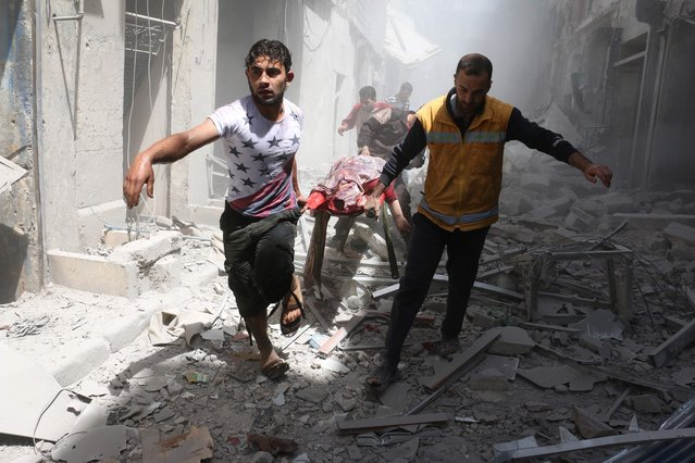 Syrian men carry a body on a stretcher amid the rubble of destroyed buildings following a reported air strike on the rebel-held neighbourhood of Al-Qatarji in the northern Syrian city of Aleppo, on April 29, 2016. Fresh bombardment shook Syria's second city Aleppo, severely damaging a local clinic as outrage grows over an earlier air strike that destroyed a hospital. The northern city has been battered by a week of air strikes, rocket fire, and shelling, leaving more than 200 civilians dead across the metropolis. The renewed violence has all but collapsed a fragile ceasefire deal that had brought an unprecedented lull in fighting since February 27. (Photo by Ameer Alhalbi/AFP Photo)