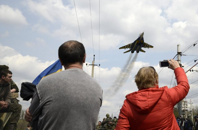 People watch a Ukrainian military jet fly above Kramatorsk, on April 16, 2014. Government forces and separatist pro-Russian militias staged rival shows of force in eastern Ukraine amid escalating rhetoric on the eve of crucial four-power talks in Geneva on the country's future. (Photo by Reuters/Stringer)