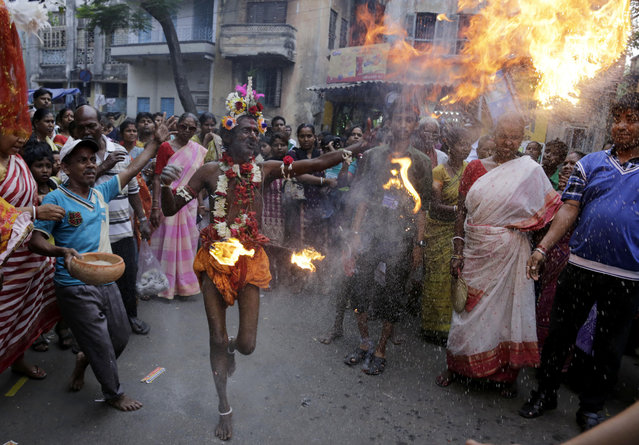 A Hindu devotee carries torches as he dances on road part of a ritual during celebrations of Shiva Gajan, a Hindu festival in Kolkata, india, Sunday, April 13, 2014. Faithful Hindu devotees offer various rituals each year in hope of winning the favor of Hindu god Shiva and fulfill their wishes. (Photo by Bikas Das/AP Photo)