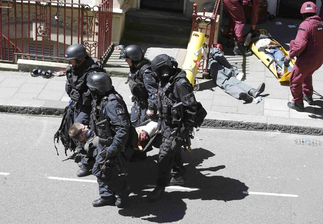 London Metropolitan Police and emergency services take part in Exercise Strong Tower, removing actors as casualties from the scene of a mock terror attack at a disused underground station in central London, Britain June 30, 2015. London police held their biggest-ever terrorism drill on Tuesday, pitting the emergency services against a group of marauding attackers, nearly 10 years since four young British Islamists killed 52 people in suicide bombings on London's transport network in July 2005. (Photo by Peter Nicholls/Reuters)