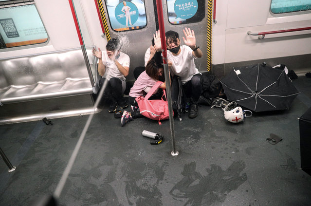 Police shoot pepper spray as they try to detain protesters inside a train at Prince Edward MTR Station, Hong Kong, Saturday, August 31, 2019. Hundreds of people are rallying in an athletic park in central Hong Kong as a 13th-straight weekend of pro-democracy protests gets underway. (Photo by Ring Yu/HK01 via AP Photo)