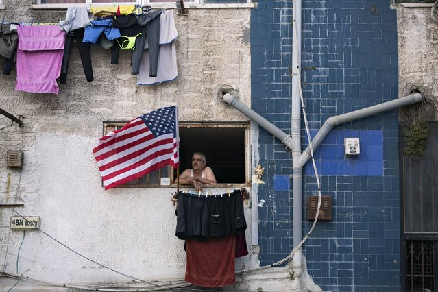 A man looks out from his apartment in Tel Aviv, Israel, Saturday, May 7, 2016. (Photo by Oded Balilty/AP Photo)