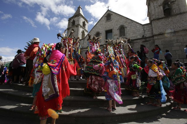In this June 4, 2015 photo, a group of dancers enter the church, beginning the start of the Corpus Christi festival, in Pujili, Ecuador. (Photo by Dolores Ochoa/AP Photo)
