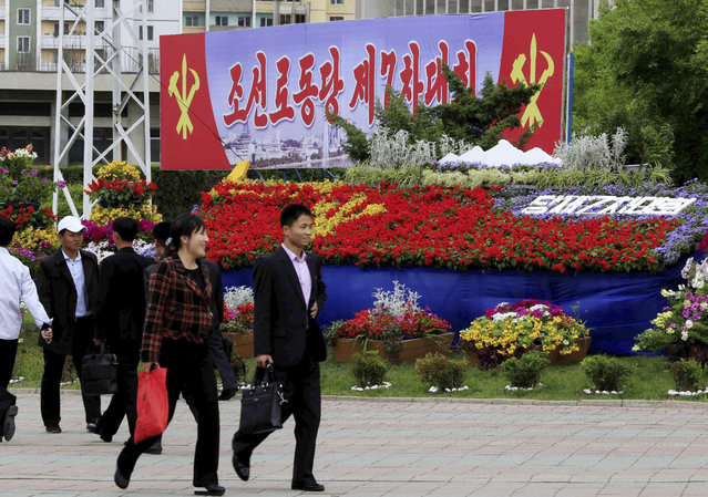 """Pedestrians walk by a flower arrangement and billboard with the words """"The 7th Congress of the Workers' Party of Korea"""" Thursday, May 5, 2016, in Pyongyang, North Korea. (Photo by Kim Kwang Hyon/AP Photo)"""