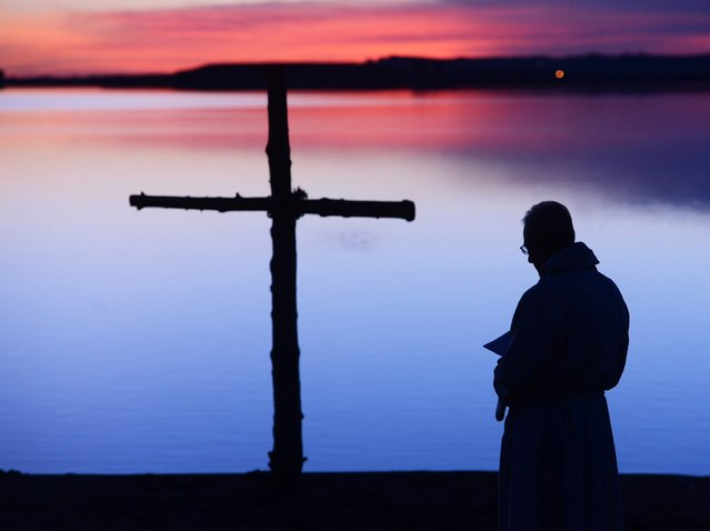 The Rev. Mark Twietmeyer, of Trinity Lutheran Church, stands before the sermon at the Boulder Reservoir for the Easter Sunrise Service on Sunday, April 20, 2014, in Boulder, Colo. (Photo by Cliff Grassmick/AP Photo/The Daily Camera)