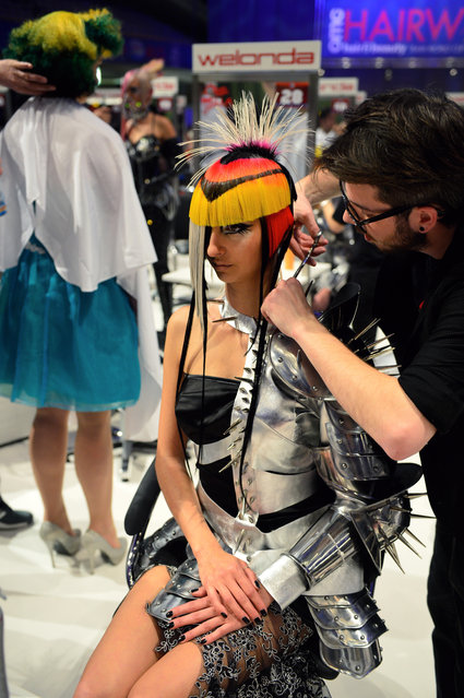 """A hairdresser styles his model during the contest """"Full Fashion Look"""" at the OMC Hairworld World Cup on May 4, 2014 in Frankfurt am Main, Germany. (Photo by Thomas Lohnes/Getty Images)"""