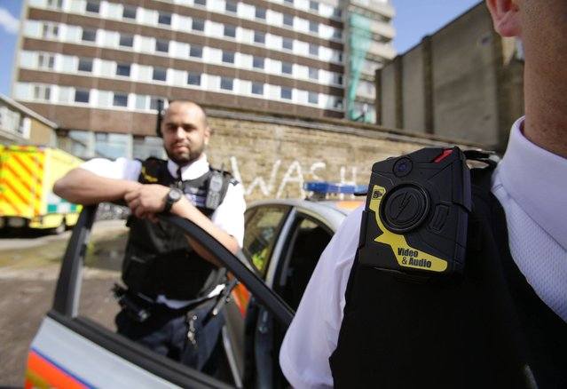Constable Yasa Amerat (left) and Constable Craig Pearson wearing their body-worn video (BWV) cameras, ahead of a year-long pilot scheme by the Metropolitan police, at Kentish Town in London, on May 6, 2014. (Photo by Yui Mok/PA Wire)