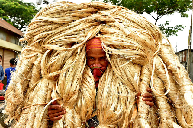 A labourer carries bundles of jute at a wholesale market in Central Bangladesh on August 2, 2019. (Photo by Xinhua News Agency/Barcroft Media)