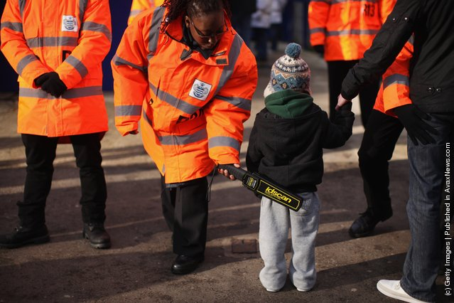 A young Queen's Park Rangers fan is searched with metal detector before entering the family stand at the Loftus Road stadium
