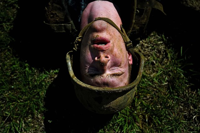 A member of the United States Naval Academy freshman class shows his exhaustion at the wet and sandy station during the annual Sea Trials training exercise at the U.S. Naval Academy on May 13, 2014 in Annapolis, Maryland. (Photo by Patrick Smith/Getty Images)