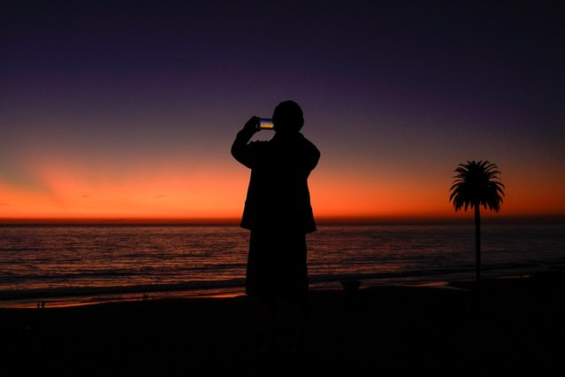 A man uses his phone to take a picture of the sky after sun set in Encinitas, California, U.S. October 7, 2019. (Photo by Mike Blake/Reuters)