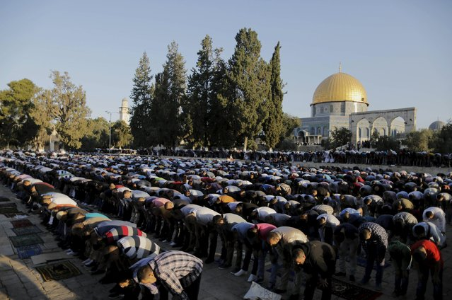 Palestinian men pray on the first day of the Muslim holiday of Eid al-Fitr, which marks the end of the holy month of Ramadan, near the Dome of the Rock at the compound known to Muslims as the Noble Sanctuary and to Jews as Temple Mount, in Jerusalem's Old City July 17, 2015. (Photo by Ammar Awad/Reuters)