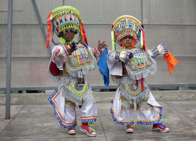 "Young ""scissors"" dancers pose after performing in a national scissors dance competition at Lima's Exposition Park, May 18, 2014. The Danza de las tijeras, or scissors dance, is a traditional dance from the Peruvian southern region of the Andes, in which two or more performers take turns dancing while accompanied with music from a harp and a violin. Dancers would display various skills and moves, which include cutting the air with the use of a scissors. (Photo by Enrique Castro-Mendivil/Reuters)"