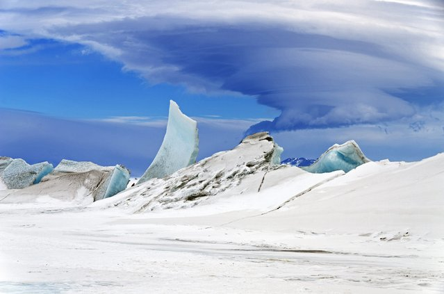 A handout picture made available by NASA on 13 May 2014 shows a multi-layered lenticular cloud hovering near Mount Discovery, a volcano about 70 km southwest of McMurdo Station on Ross Island, Antarctica, 24 November 2013. (Photo by Michael Studinger/EPA)