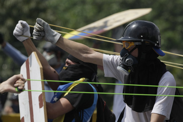 Anti-government protesters aim homemade sling shots during clashes with security forces in Caracas, Venezuela, Wednesday, May 10, 2017. (Photo by Fernando Llano/AP Photo)