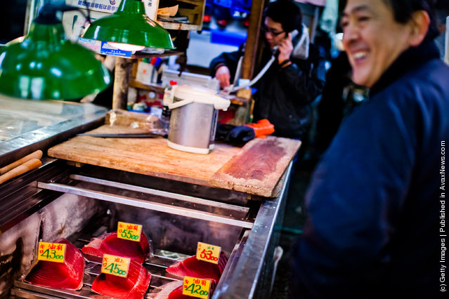 A shopkeeper smiles as he speaks with customers at the Tsukiji fish market