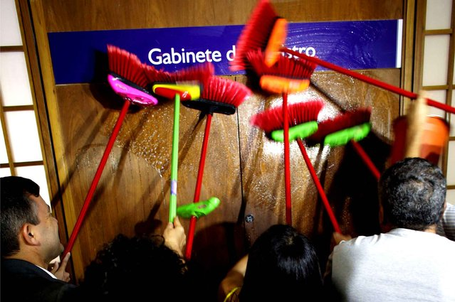 Ministerial staff use brooms to scrub the office door of the Transparency Minister Fabiano Silveira demanding his resignation, in Brasilia, Brazil, Monday, May 30, 2016. A recording TV Globo broadcast late Sunday shows Silveira criticizing Operation Car Wash, a wide-ranging corruption probe of the state oil company Petrobras that has implicated numerous leading Brazilian politicians and businessmen. Protesters in Brazil use brooms as a representation to sweep away corruption. (Photo by Eraldo Peres/AP Photo)