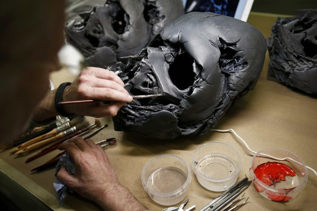 "A technician at Propshop adds finishing touches to a replica of Darth Vader's melted helmet from ""Star Wars: The Force Awakens"", in the Propshop headquarters at Pinewood Studios near London, Britain May 25, 2016. (Photo by Peter Nicholls/Reuters)"