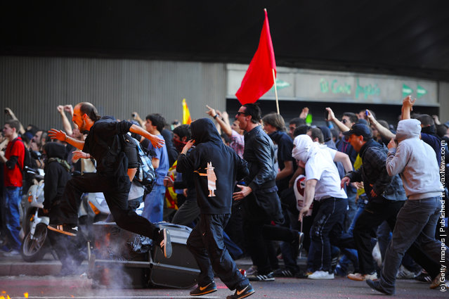 Demonstrators charge riot police during heavy clashes with riot police during a 24-hour strike on March 29, 2012 in Barcelona, Spain