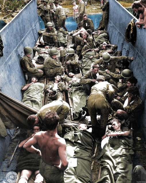 Wounded troops lying on stretchers aboard a lighter in Munda Point, New Georgia. There were more than 36 million casualties during the War in the Pacific. (Photo by Royston Leonard/Mediadrumworld)