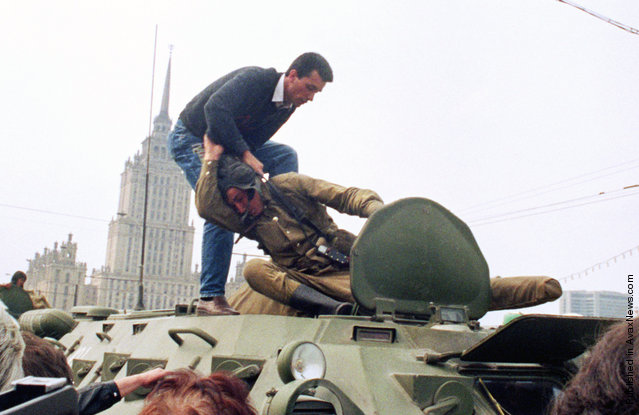 A pro-democracy demonstrator fights with a Soviet soldier on top of a tank parked in front of the Russian Federation building on August 19, 1991, after a coup toppled Soviet President Mikhail Gorbachev. The same day, thousands in Moscow, Leningrad, and other cities answered Russian Republic President Boris Yeltsin's call to raise barricades against tanks and troops