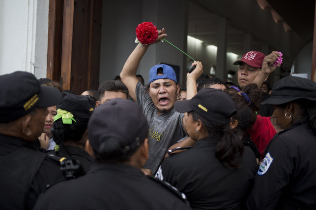 A man has an altercation with several police officers as he demands entrance into the dancing area where promise keepers dance with an image of Managua's patron saint Santo Domingo de Guzman in Managua, Nicaragua, Saturday, August 1, 2015. (Photo by Esteban Felix/AP Photo)