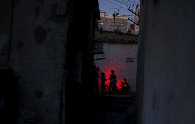 Palestinian children play as they use a torch during power cut at Shatti (beach) refugee camp in Gaza City July 23, 2015. (Photo by Mohammed Salem/Reuters)