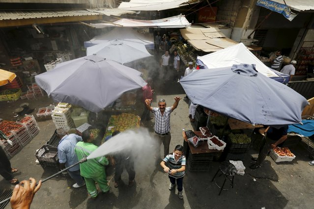 Residents react react as Greater Amman Municipality personnel spray them with a water sprinkler in order to cool them down as part of measures to ease the effect of a heatwave, in Amman, Jordan, August 3, 2015. (Photo by Muhammad Hamed/Reuters)